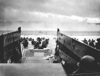 U.S. troops on D-Day at Omaha Beach. | Public domain; official U.S. Coast Guard photograph