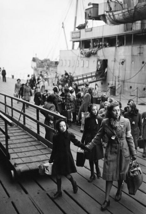 DUTCH CHILD REFUGEES: ARRIVAL IN BRITAIN AT TILBURY. 1945. A Dutch school teacher leads a group of refugee children away from the ship upon which they have just arrived. They have berthed at Tilbury Docks and will be taken to a rest centre, before onward transport to a hostel. | Imperial War Museum