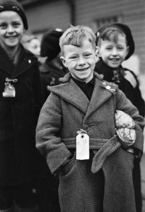 DUTCH CHILD REFUGEES: ARRIVAL IN BRITAIN AT TILBURY. 1945. A small Dutch boy smiles for the camera upon arrival at Tilbury. He is carrying a small paper parcel under his arm, which contains all his luggage. He, and the other children, (some of whom can be seen behind him) all have labels pinned to their coats which bear their names, home address and destination. | Imperial War Museum
