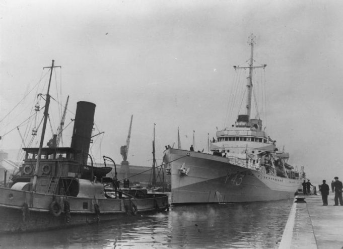 HMS BANFF. Coming alongside at Tilbury with tug BADIA | Imperial War Museum