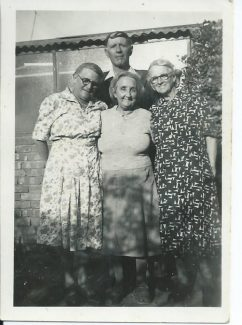 My great grandmother Minnie in the middle standing in front of her husband George. I'm assuming that both the women standing either side of her are her sisters, Annie and Lizzie (Eliza) photo taken obviously before George's death in June 1951. Photo taken in Newcastle, NSW Australia.