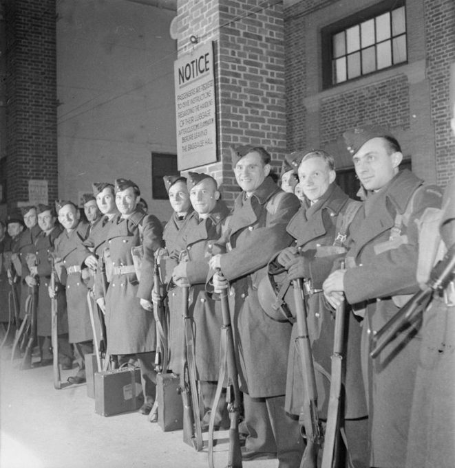POLISH TROOPS REPATRIATED FROM TILBURY: TRANSPORT OF TROOPS ABOARD THE 'BANFORA', TILBURY. 1945. Polish airmen line up with their luggage and rifles as they wait to board the SS Banfora. | Imperial War Museum