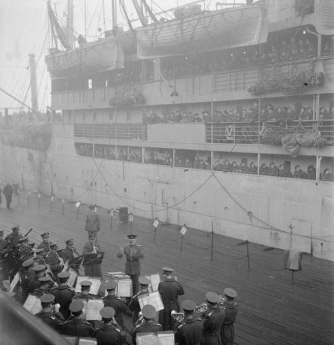 REPATRIATION OF POLISH TROOPS FROM BRITAIN TO POLAND, 1945-1948 A scene at Tilbury docks: on the dockside, the Guards band entertains the thousands of Polish troops on board the SS BANFORA, moored alongside, as they wait to depart from England. Many of them would face prosecution at the hands of communist regime for serving alongside the Western Allies. | Imperial War Museum