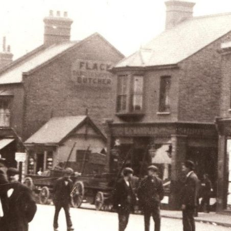 The Tin Hut Barbers, below Flack Butchers sign