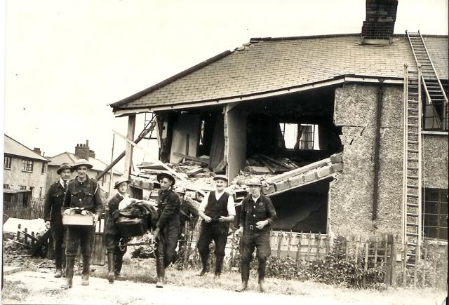 House in Feenan Highway, Tilbury Town, hit by a high explosive bomb. Civil defence workers helped to rescue furniture and belongings. | Thurrock Museum