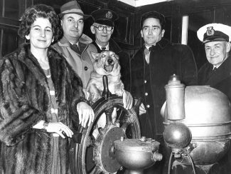 Captain &  Mrs L.H.R Wheeler on the bridge of the ferry 'Mimi' for the last trip  Captain Wheelers Corgi Taffi has his paws on the wheel, also in the picture is  Captain Harrison who navigated the last crossing  and Mates A Gate and C. Regan. | Grays Library collection